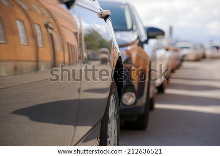 Row of parked cars with reflection of buildings on opposite side of the street