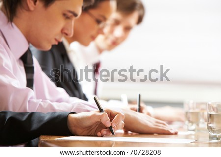 Row of people writing in board room - stock photo