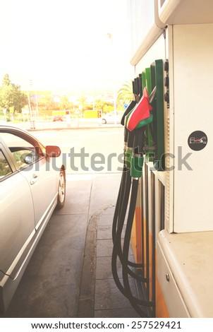 row of petrol station pupmps and car close up, retro toned - stock photo