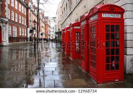 Row of phone booths in rainy London. Street view.