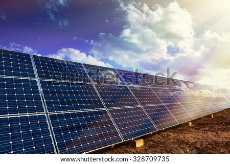 Row of photo voltaic solar panels and sunbeam