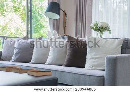 row of pillows on modern grey sofa in living room - stock photo