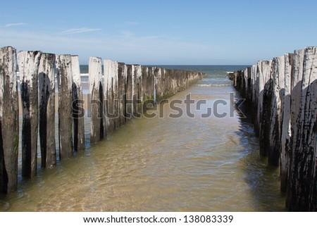 Row of poles to break the waves - stock photo