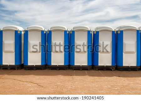 row of portable public wc in the street - stock photo