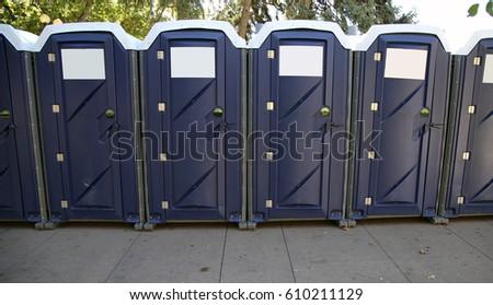 Row Of Portable Toilets On City Street