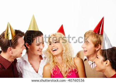 Row of positive people in birthday caps laghing and having fun - stock photo