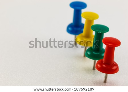 row of push pins on white background