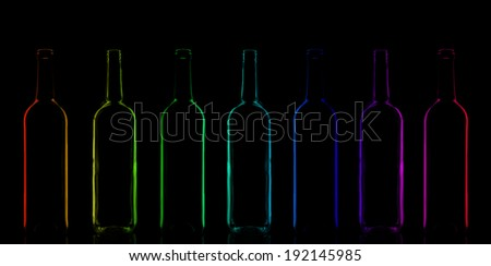 Row of rainbow colored bottles composition in a low-key lighting - stock photo