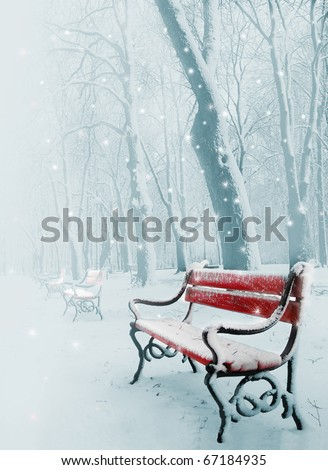 Row of red benches in the park in the snow in winter