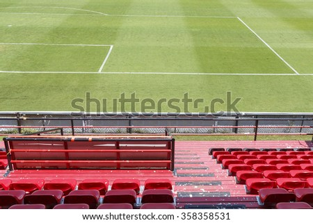Row of red chairs in football stadium and field - stock photo