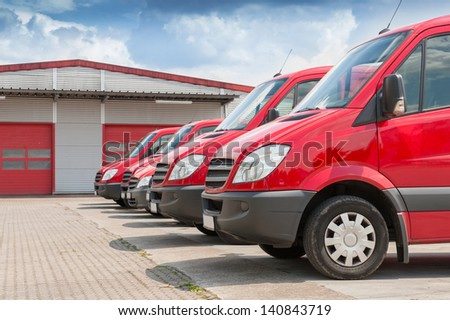 Row of red delivery and service van, trucks and cars in front of a factory and warehouse distribution plant - stock photo