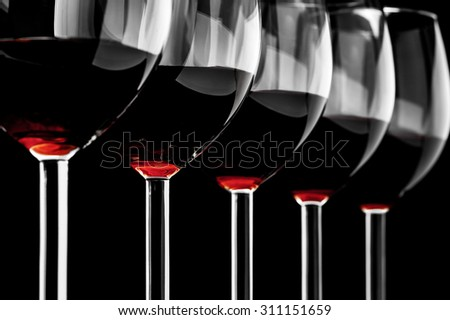 Row of red wine glasses  on a black background in horizontal format