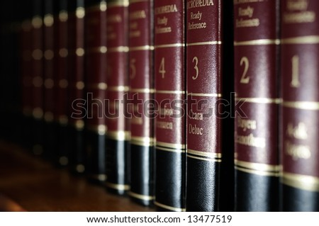 Row of reference books on library shelf - stock photo