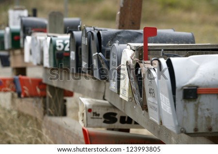 Row of rural mailboxes, one with red flag up indicating mail to be sent. - stock photo