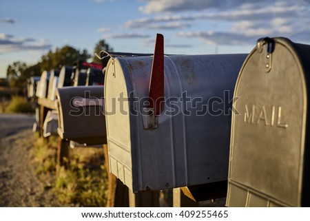 Row of rural mailboxes one  with the flag up with shallow depth of field - stock photo
