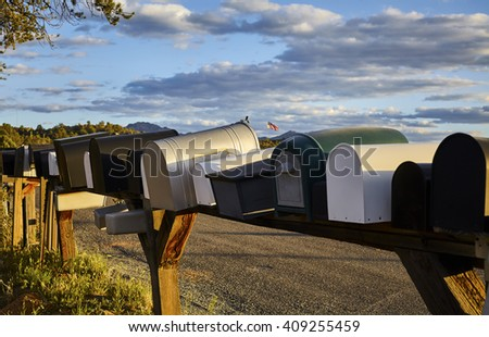 Row of rural mailboxes with an American Flag in the distance - stock photo
