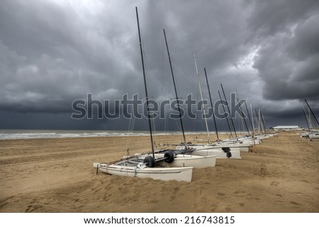 Row of sail boats on the beach under a dark sky in Holland - stock photo