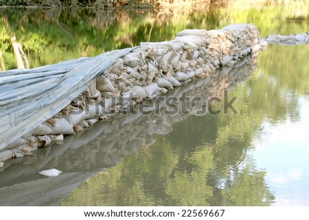 Row of sandbags in flood waters. - stock photo