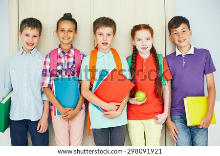 Row of schoolmates with books looking at camera - stock photo