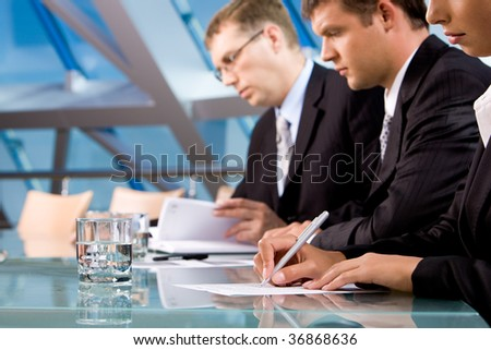 Row of serious business people making notes during conference - stock photo