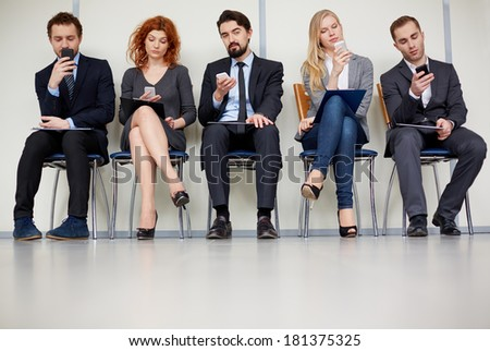 Row of several business partners using mobile phones - stock photo