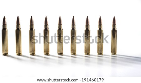 Row of shiny rifle bullets isolated on white with shadows - stock photo
