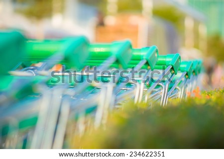 Row of shopping cart with green handles near live natural fence on parking near supermarket - stock photo