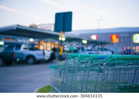 Row of shopping carts at entrance of supermarket near parking lot