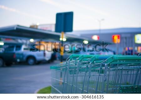Row of shopping carts at entrance of supermarket near parking lot - stock photo