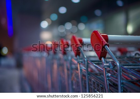 Row of shopping carts on winter street at evening near store - stock photo