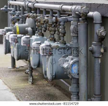 Row of Six gray gas meters manifolded together next to a building - stock photo