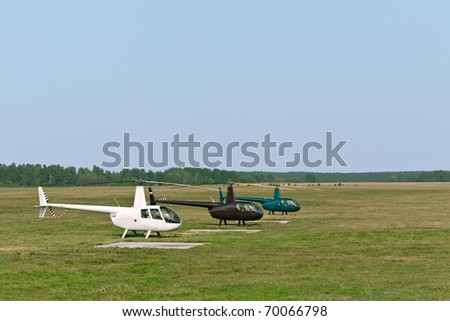 Row of small helicopters at airfield