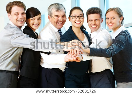 Row of smiling co-workers making pile of hands and looking at camera - stock photo