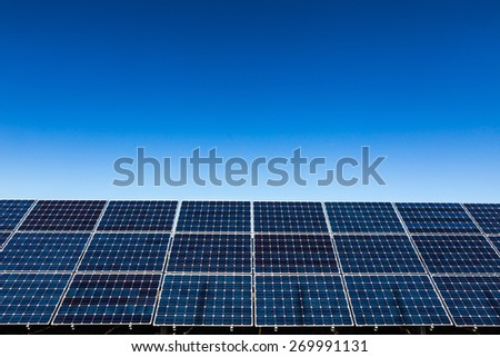 Row of solar panels and clear blue sky background - stock photo