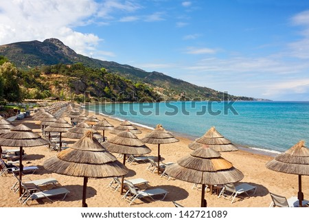 Row of Straw umbrellas and lounges at sandy beach  Zakynthos, Greece. - stock photo