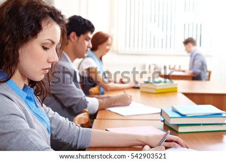 Row of students studying in classroom in college
