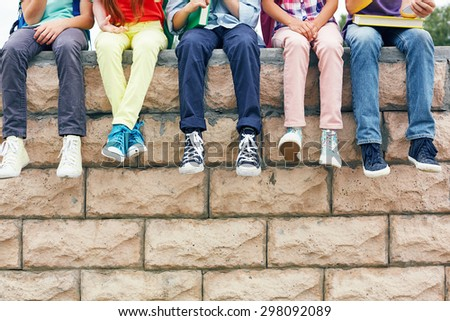 Row of successful learners looking at camera outside - stock photo