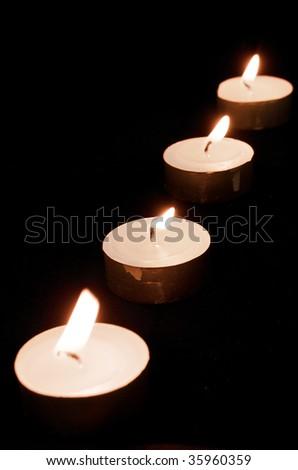 Row of Tea Lights on black background - stock photo