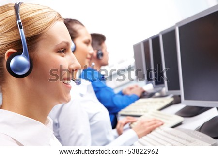 Row of telephone operators looking at the monitors and working