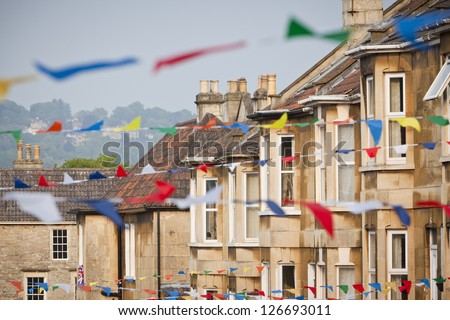 Row of terraced houses with foreground bunting fluttering in the wind. Taken at a street party celebrating the UK Royal Wedding on 29th April 2011 in Bath, England. - stock photo