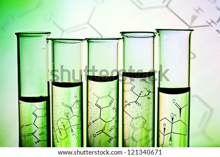 Row of test tubes in green tone. - stock photo