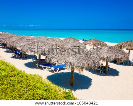 Row of thatched umbrellas at the famous Varadero beach in Cuba on a beautiful summer day - stock photo