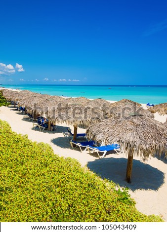 Row of thatched umbrellas at the famous Varadero beach in Cuba on a beautiful summer day (vertical orientation) - stock photo