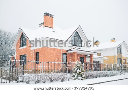Row of the snowbound houses, homes with the sidewalk on empty street in cold, chilly and frosty winter time covered with snow. Nice and comfortable neighborhood, community  in winter time.  - stock photo