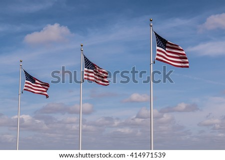Row of three American Flags with a cloudy blue sky background.