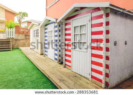 Row of three colorful beach striped huts in a home garden - stock photo