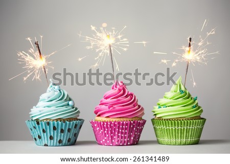 Row of three cupcakes with sparklers - stock photo