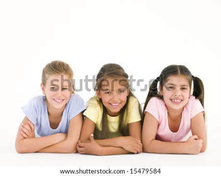 Row of three friends lying down smiling - stock photo