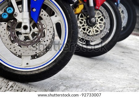 Row of three motorcycle wheels parked in a road - stock photo