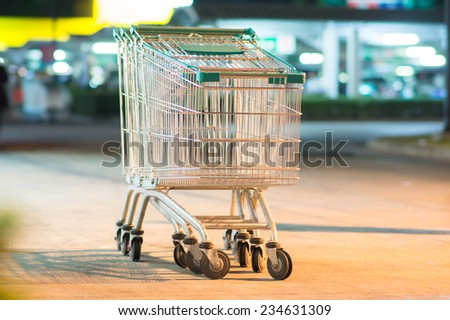 Row of three shopping carts with green handles on parking near supermarket in evening - stock photo